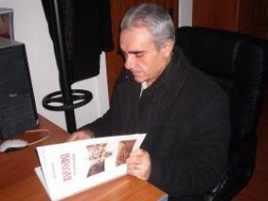 Nicolai Oprea răsfoind primul exemplar al lucrării