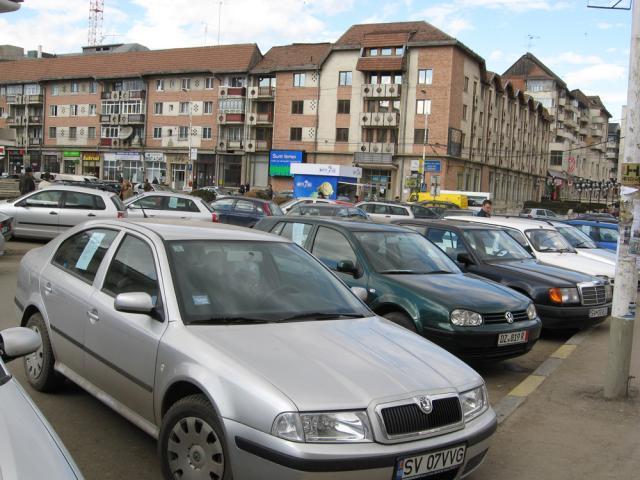 Zeci de spaţii de parcare sunt ocupate de maşini care au afişate pe ele anunţuri de vânzare