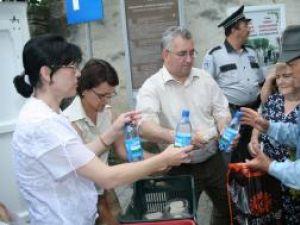 Ion Lungu şi soţia sa, împărţind sarmale şi apă credincioşilor