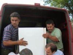 Gheorghe Flutur (dreapta) şi Dumitrul Mihalescul (stânga) distribuind ajutoare sinistraţilor