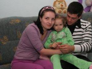 Micuţa Claudia, în braţele părinţilor săi, Valentina şi Victor Timinger