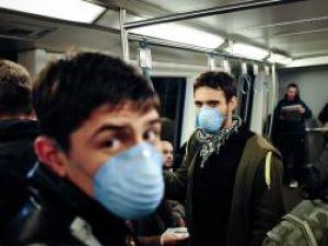 Populaţia se protejează purtând măşti. Foto: MEDIAFAX