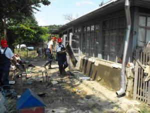 Îndepărtarea nămolului din casele inundate, cu ajutorul voluntarilor de la E.ON