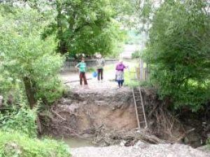 Singura cale de acces a localnicilor din zona rămasă izolată este o scară de lemn pe care oamenii au coborât-o în hăul format în locul podului