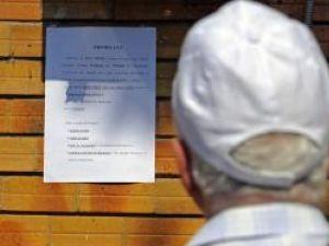 Un bărbat citeşte cum poate plăti contribuţia individuala privind asigurarea în sistemul asigurărilor pentru şomaj Foto: Mediafax