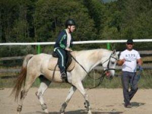 Ionel Moroşan, în timp ce îl invaţă pe unul dintre copii să meargă pe cal