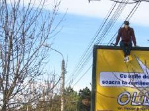 Panoul publicitar a atras atenţia trecătorilor, surprinşi de imaginea tânărului cocoţat