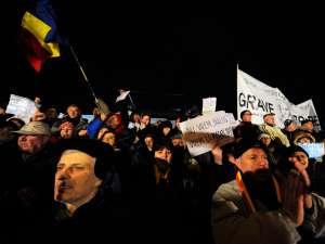 Persoane din  Piaţa Universităţii strigă lozinci contra preşedintelui Traian Basescu şi în favoarea alegerilor anticipate. Foto: MEDIAFAX