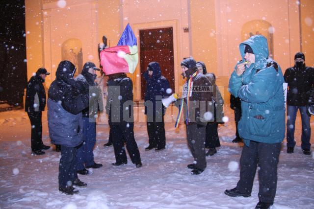Cei aproximativ două zeci de protestatari au avut mesaje adaptate la ninsoarea şi frigul de afară
