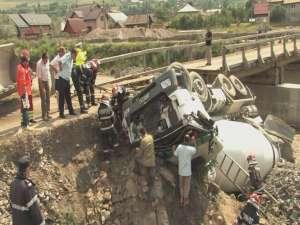 Şoferul a pătruns cu vehiculul greu, încărcat, pe un pod din lemn care a cedat, răsturnându-se în albie