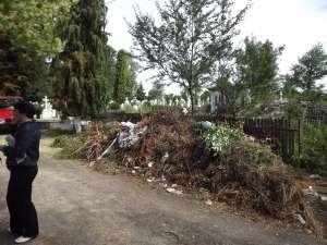 Intrarea în cimitir, străjuită de un morman de gunoi