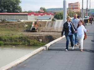 O mulţime de oameni traversează podul într-o zonă fără nici o protecţie
