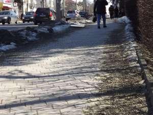 Nisipul şi pietrişul date ca antiderapant pe trotuarul din fata Primăriei Suceava