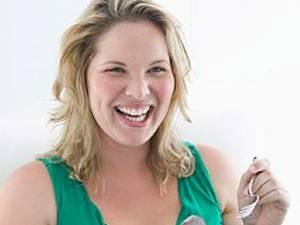 Persoanele care mănâncă pe fond emoţional consumă mai multe alimente bogate în calorii atunci când sunt fericite. Foto: CORBIS