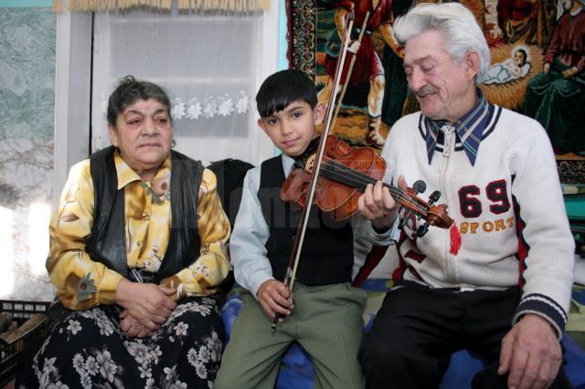 Străbunicii Tereza si Mihai, alături de Loris, acum 6 ani, când a primit în dar o vioară