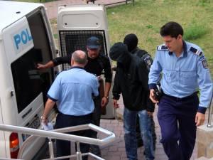 Fostul poliţist Olinici (cu gluga pe cap) şi Mihai Halip împart aceeaşi pereche de cătuşe