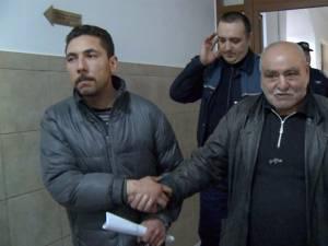 """""""Norocel"""" (stânga) şi tatăl său, duşi de poliţişti în sala de judecată, cu câteva minute înainte de a fi arestaţi preventiv"""