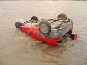 Autoturismul a plonjat în apă, unde s-a răsturnat, tânărul rămânând captiv în maşină