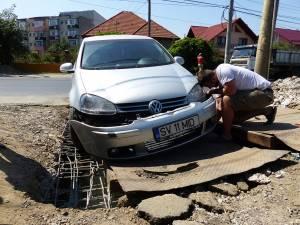 Maşina avariată după ce placa de fier pusă peste zona în care se lucrează a alunecat