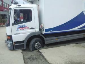 Camionul de transport marfă a rămas împotmolit într-un şanţ proaspăt acoperit