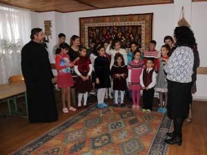 Copiii cântă împreună cu părintele şi preoteasa Mioara cântece pentru Moş Nicolae