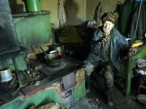 Alexandru Moldovan se deplasează cu greutate, târându-se pe genunchi, iar în casa unde îşi duce traiul este o mizerie greu de imaginat