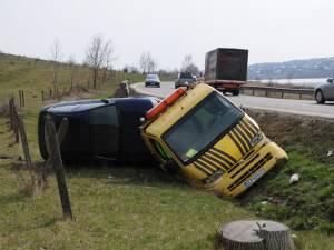 În urma impactului, autoutilitara s-a răsturnat în afara drumului iar autoturismul de pe platformă a fost şi el avariat