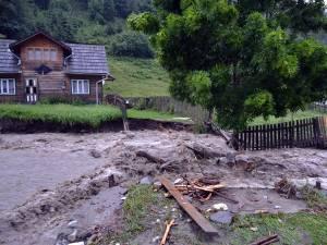 Apa învolburată a distrus podeţe şi porţiuni de drumuri comunale, lăsând zeci de case izolate