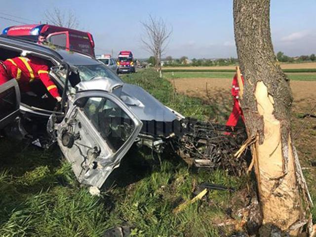 În urma impactului cu copacul de pe marginea drumului, bărbatul de 53 de ani aflat pe scaunul din dreapta a rămas încarcerat în maşină