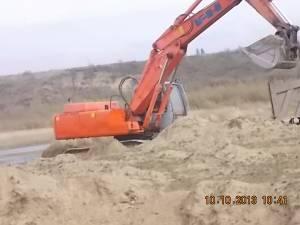 Excavatorul firmei, surprins în timp ce săpa pe malul râului Siret