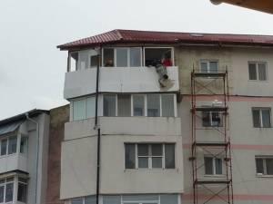 """""""Batman""""-ul Dorel, lucrând la izolarea termică a unui balcon aflat la etajul cinci al clădirii, ţinut de haină de un coleg"""