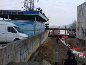 Dan Ioan Cușnir arată că cetăţenii sunt nevoiţi să meargă prin noroaie pentru a ajunge la pasarela de sub podul peste râul Suceava