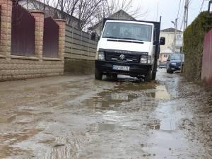 Strada din cartierul Laniște este plină de gropi umplute cu apă, prin care se circulă cu greutate