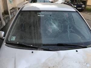 Mașina avariată de tencuiala căzută de pe bloc în bucăți mari