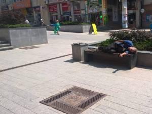 Om al străzii dormind pe bancă în centrul Sucevei