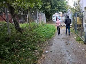 """Cușnir îi arată primarului Ion Lungu cărarea de pământ pe care circulă către şcoală elevii Colegiului """"Mihai Eminescu"""""""