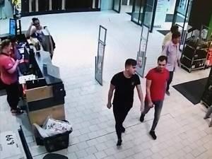 Doi tineri îmbrăcaţi bine intră în magazin relaxaţi şi apoi se opresc la raionul auto