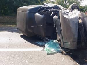 O furgonetă implicată în accident a rămas răsturnată în mijlocul drumului