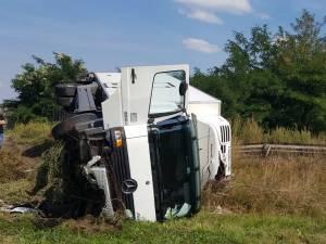 În urma impactului puternic, autocamionul s-a răsturnat pe acostamentul drumului