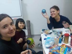 Copiii și voluntarii  pregătesc obiectele care vor fi scoase la vânzare la Târgul de Crăciun