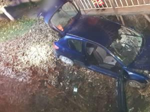 Mașină răsturnată în albia unui pârâu. Șoferul, găsit încarcerat, prins sub bord