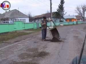 Satul în care oamenii s-au transformat în drumari şi acoperă gropile din asfalt cu pământ