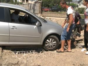Stradă din Suceava, în şantier, capcană pentru maşini şi locul în care muncitorii lucrează sub protecţia unui agent de pază