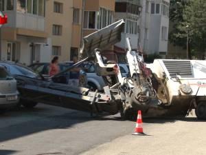 Un utilaj de frezat asfaltul s-a răsturnat peste două maşini