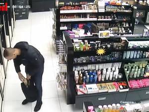 Hoț filmat în timp ce fură parfumuri de lux dintr-un magazin