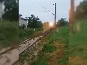 Tren cu călători, blocat de apă și aluviuni